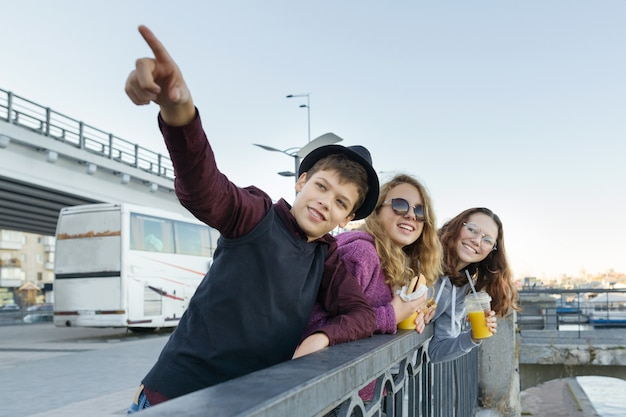 Lifestyle of adolescents, boy and two teen girls are walking in the city