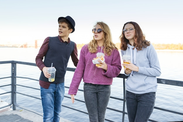 Lifestyle of adolescents, boy and two teen girls are walking