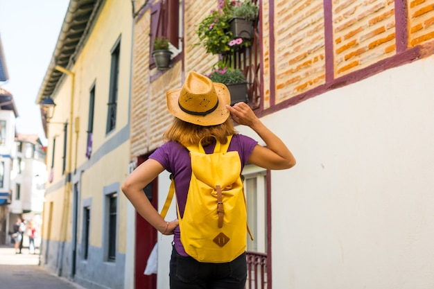 Lifestyle, an adventurous hiker with a yellow backpack visiting a traditional rural village, copy and paste space, municipality of ea in the basque country