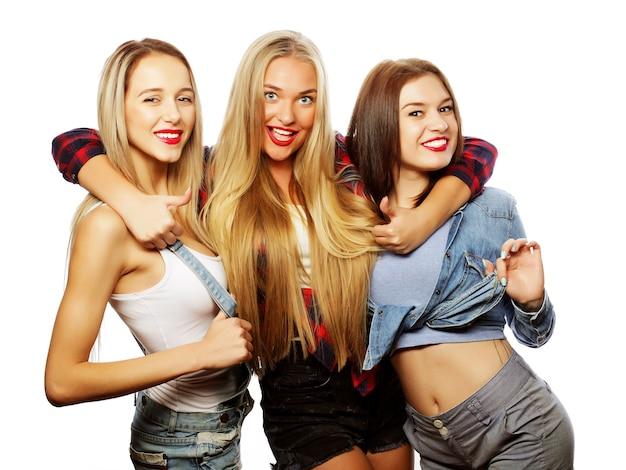 ライフスタイルと人々の概念:白い背景の上に、3人のスタイリッシュなセクシーな女の子の親友のファッションの肖像画。楽しみのための幸せな時間。