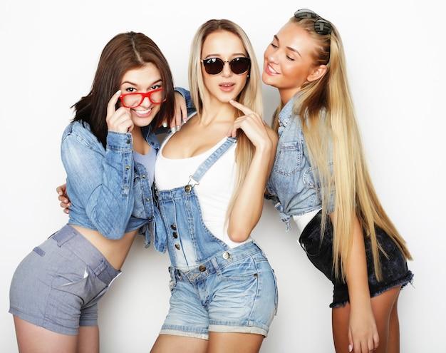 Образ жизни и люди концепции: модный портрет трех лучших друзей стильных сексуальных девушек, на белом фоне. счастливое время для удовольствия.