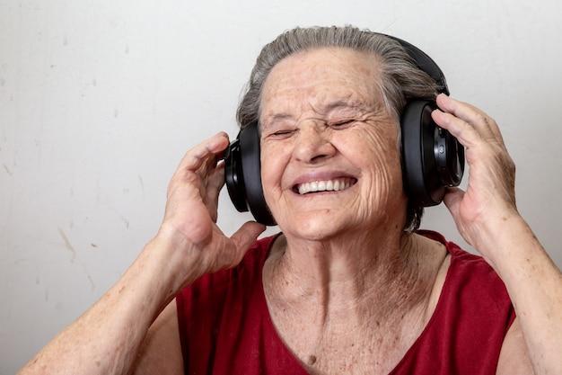 ライフスタイルと人々の概念:面白い老婦人は音楽を聴くと白い背景の上で踊る。眼鏡をかけて彼のヘッドフォンで音楽を聴くに踊る高齢者の女性。