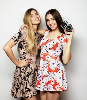 Концепция образа жизни и людей: счастливые девушки-друзья делают несколько снимков с камерой на сером фоне