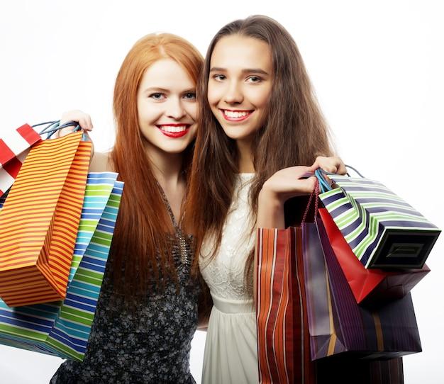 Концепция образа жизни и людей: портрет двух красивых молодых женщин с хозяйственными сумками