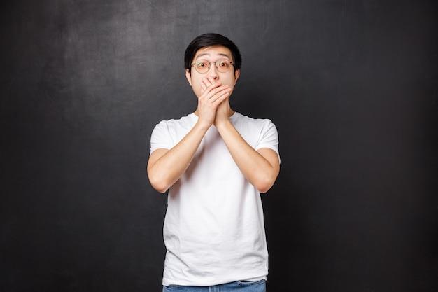 Концепция образа жизни и людей. безмолвный встревоженный и испуганный молодой азиатский парень обнаружил что-то страшное, задыхаясь прикрыв рот в панике, уставившись в камеру, вытащил глаза, полные страха,
