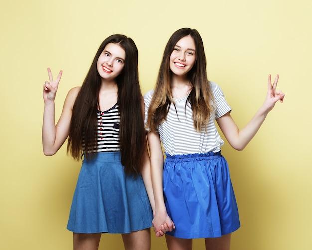 Концепция образа жизни и людей: две молодые девушки друзья стояли вместе и веселились. глядя на камеру. желтый фон.