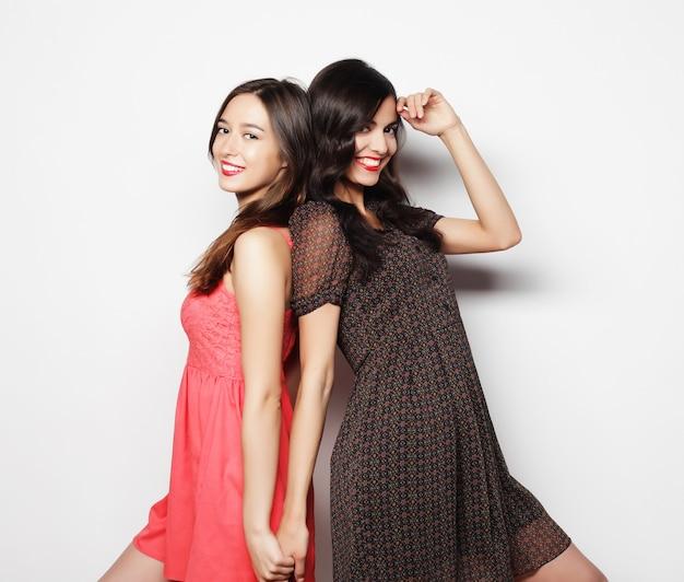 Концепция образа жизни и людей: две молодые девушки друзья стояли вместе и веселились. смотрю в камеру.