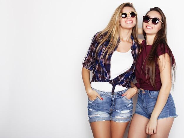 ライフスタイルと人々のコンセプト:一緒に立って楽しんでいる2人の若いガールフレンド。カメラを見てください。