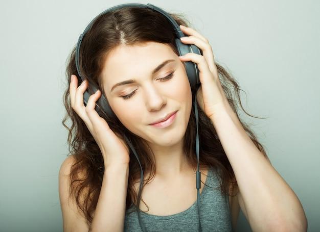 ライフスタイルと人々の概念:音楽を聴くヘッドフォンを持つ若い幸せな女性。