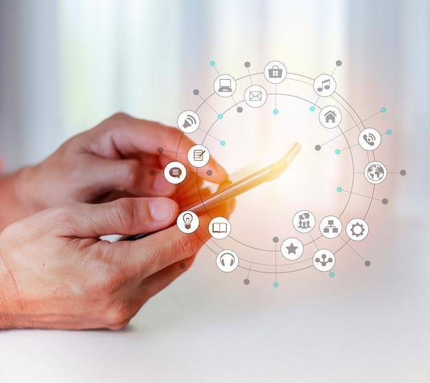 ライフスタイルとテクノロジーの概念スマートフォンとソーシャルメディアのサイクルチャートの背景で男の手を閉じる