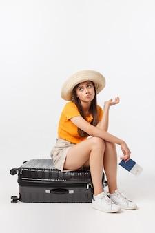 ライフスタイルと旅行の概念:若い美しい白人女性は、スーツケースの上に座って、彼女の飛行を待っています。白で隔離
