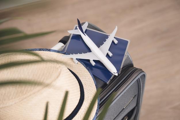 ライフスタイルと旅行のコンセプト。灰色のスーツケースにパスポート、帽子、模型飛行機