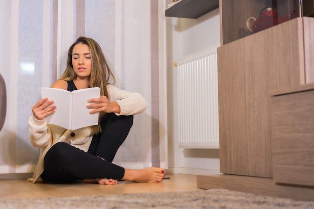 집에서 라이프 스타일, 커피와 함께 젊은 금발 백인 여자는 바닥에 앉아 그녀의 거실에서 책을 읽고 웃고