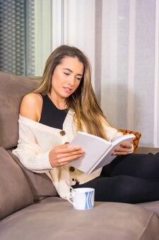 집에서 라이프 스타일, 커피가 그녀의 거실에서 소파에 책을 읽고 즐기는 젊은 금발의 백인 여자