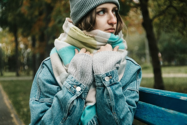 Lifestyle autumn portrait of young adult woman sitting on a bench wrapped herself in warm scarf