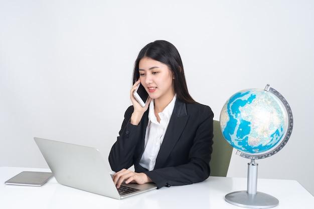 ライフスタイル美しいアジアビジネス若い女性のオフィスの机の上にラップトップコンピューターとスマートフォンを使用して