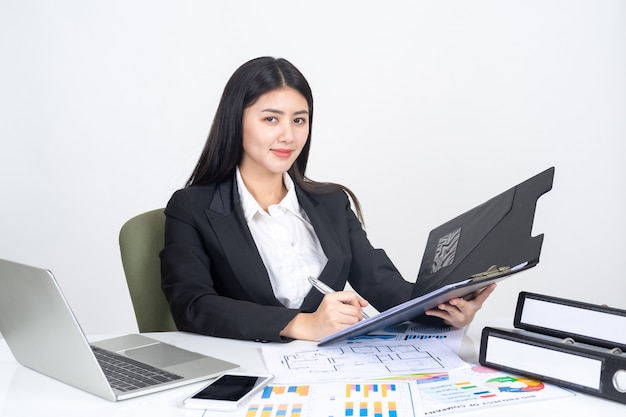 Lifestyle beautiful asian business young woman using laptop computer and smart phone on office desk