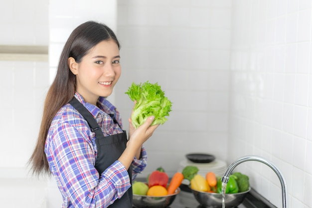 Lifestyle beautiful asian healthy girl fill happy, washing vegetables in the kitchen sink