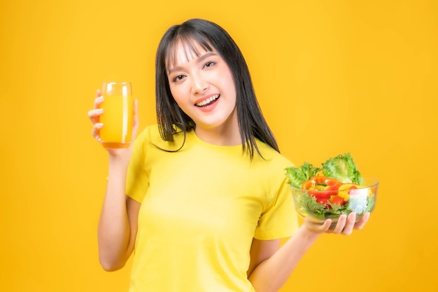 Lifestyle beautiful beauty asian woman cute girl with bangs hair style in in yellow t shirt feel happy enjoy eating diet food fresh salad and orange juice for good health isolated on yellow background