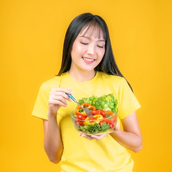 Lifestyle beautiful beauty asian woman cute girl with bangs hair style in in yellow t shirt feel happy enjoy eating diet food vegetable fresh salad for good health isolated on yellow background