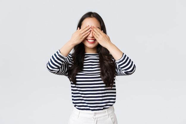라이프 스타일, 아름다움, 패션, 사람들의 감정 개념. 놀라움을 기대하는 꿈꾸는 듯한 화려한 아시아 소녀. 아시아 여성은 눈을 감고 미소를 지으며 선물을 받기 위한 신호를 기다리고 있습니다.