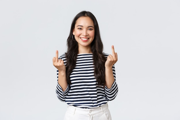 라이프 스타일, 아름다움, 패션, 사람들의 감정 개념. 근심없고 부주의한 젊은 행복한 웃는 여성은 가운데 손가락을 보여주고 기분이 좋은 흰색 배경을 보여주려 하지 않습니다.