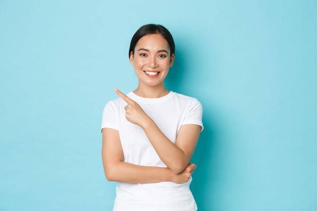 ライフスタイル、美容、ショッピングのコンセプト。明るい自信を持って笑顔で美しい幸せなアジアの女の子、左上隅を指して広告を表示し、青い壁にプロモーションのオファーを出す
