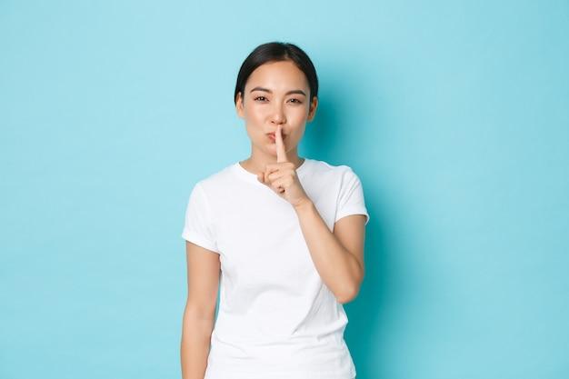 ライフスタイル、美容、ショッピングのコンセプト。官能的で夢のようなアジアの女の子は秘密を守り、うわさ話をし、青い壁の上に立ち、口の上で指で黙って、静かにしてほしいと頼みます。