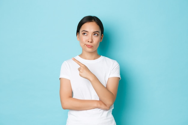 ライフスタイル、美容、ショッピングのコンセプト。左上隅を指している白いtシャツを着た懐疑的で面白くないアジアの女性は、何かを判断し、青い壁に立っている不快感を与えました。