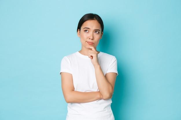 ライフスタイル、美容、ショッピングのコンセプト。思慮深く、当惑したアジアの女の子が考え、深刻な決定を下し、左上隅を見て、熟考し、青い壁を選びます
