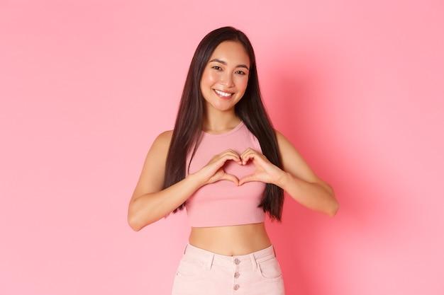ライフスタイル、美容、女性のコンセプト。ピンクの壁の上に立って、心のジェスチャーを示す夏服で素敵なブルネットアジアの女の子の肖像画、誰かのように愛やケアを表現