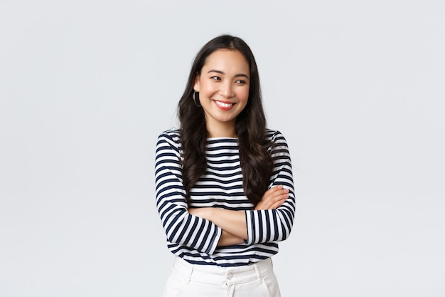 Lifestyle, beauty and fashion, people emotions concept. cheerful cute and shy asian girl cross arms chest modest pose, looking away as laughing and smiling silly, stand white background