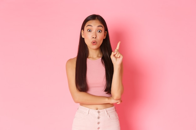 Concetto di stile di vita, bellezza e donne. la ragazza asiatica attraente creativa in abiti estivi ha una soluzione, alza il dito indice e dice la sua idea, pensa a un grande piano, in piedi muro rosa