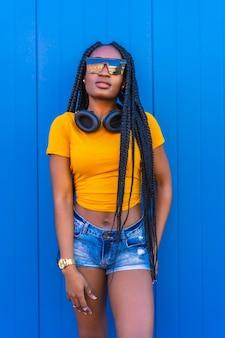黄色のtシャツとサングラスのライフスタイル、長い三つ編みの黒い女の子。笑顔のヘッドフォンでセクシーな女の子とdj