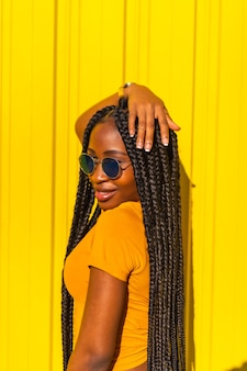 ライフスタイル、長い三つ編み、黄色のtシャツ、黄色の壁に短いジーンズを着た黒人の女の子。魅惑的な視線、ストリートスナップで魅力的なファッショナブルなポーズ