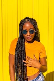 Образ жизни, черная девушка с длинными косичками, желтыми футболками и короткими джинсами на желтой стене. модная поза привлекательной с соблазнительным взглядом