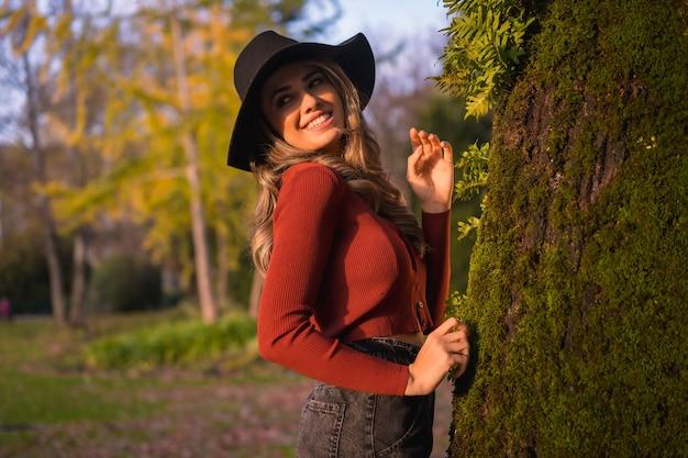 Образ жизни белокурая кавказская девушка в красном свитере и черной шляпе, наслаждаясь природой в парке с деревьями на красивом осеннем портрете молодой женщины рядом с деревом с мхом