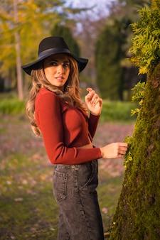 Образ жизни блондинка кавказская девушка в красном свитере и черной шляпе, наслаждаясь природой в парке с деревьями портрет молодой женщины, смотрящей на красивое дерево со мхом осенью