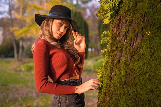 Образ жизни блондинка кавказская девушка с красным свитером и черной шляпой, наслаждаясь природой в парке с деревьями портрет молодой женщины рядом с красивым деревом осенью со мхом
