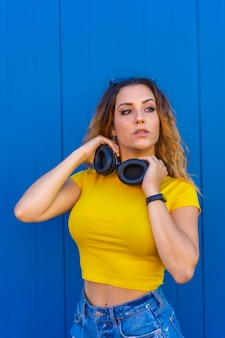 Lifestyle, blonde caucasian girl with yellow t-shirt. sexy girl and dj with headphones smiling