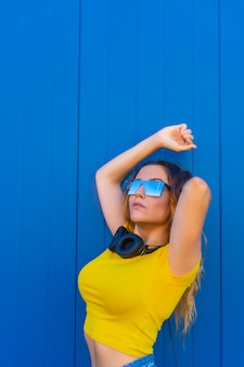 Lifestyle, blonde caucasian girl with yellow t-shirt. young woman posing with music headphones and sunglasses
