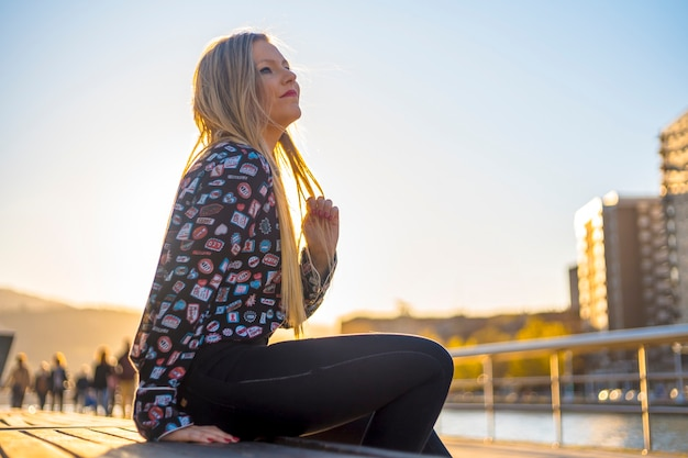 Lifestyle, blonde girl enjoying the city with a blue shirt and black pants
