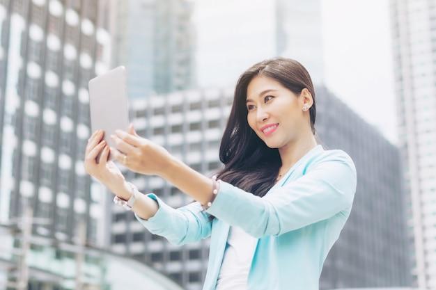 ライフスタイルビジネスアジアの女性はスマートフォンを使用して幸せを感じ、若い美しい女性はビジネス地区で自分撮り写真を撮る
