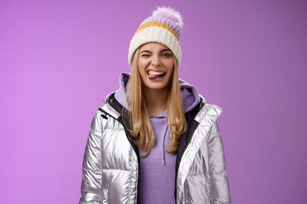 생활 양식. 건방진 평온한 즐거움을 느끼는 매력적인 금발 소녀는 멋진 스키 휴가를 즐기는 겨울은 반짝이는 재킷 세련된 모자를 광범위하게 입고 웃고 긍정적 인 쇼 혀를 즐겁게합니다.