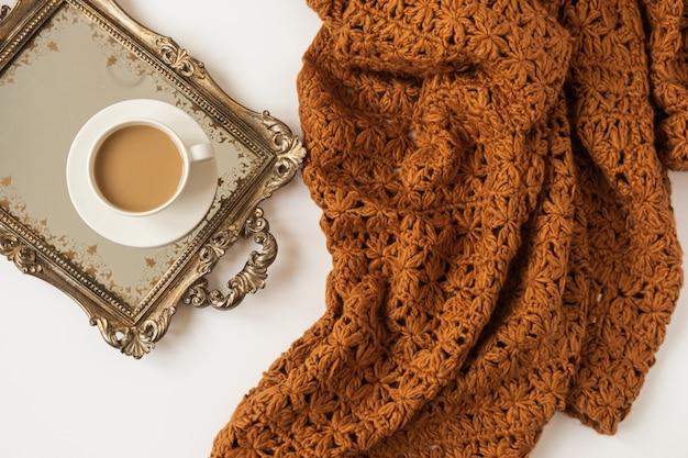 Состав образа жизни с чашкой кофе с молоком на винтажном золотом подносе и связанном коричневом пледе одеяла на белой предпосылке.