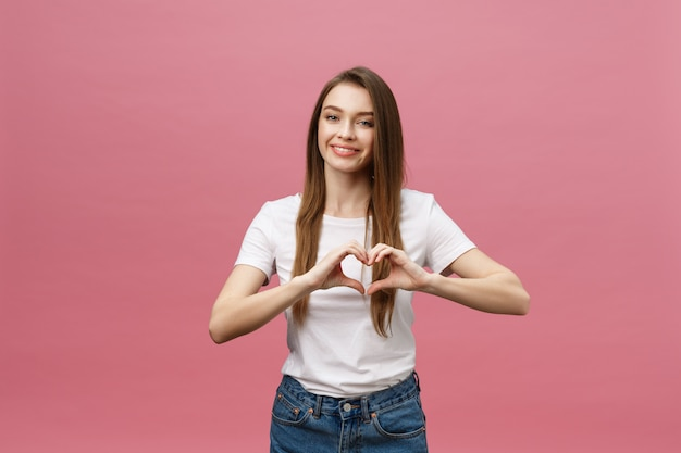 Lifestyle concept: beautiful attractive woman in white shirt making a heart symbol