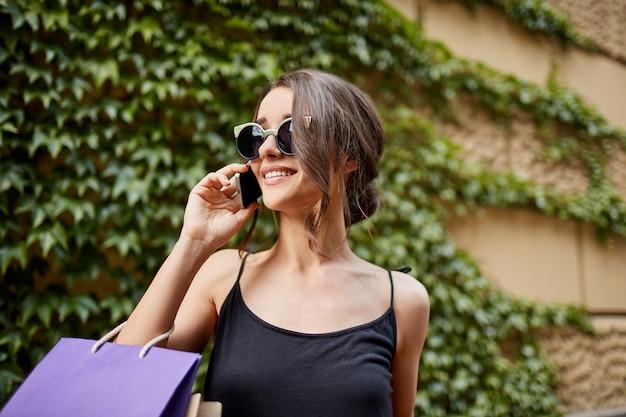 라이프 스타일 개념. 매력적인 젊은 검은 머리 백인 여자의 선글라스와 검은 드레스 미소, 행복 한 표정으로 옆으로 찾고, 어머니와 전화 통화, 쇼핑을 들고 닫습니다