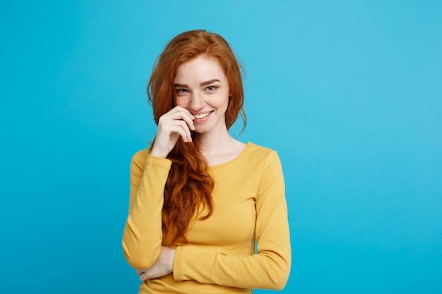 ライフスタイルの概念 - クローズアップ肖像画若い美しい魅力的なジンジャー赤毛の女の子は、彼女の髪を恥ずかしがり屋で遊んで。青いパステルの背景。スペースをコピーします。