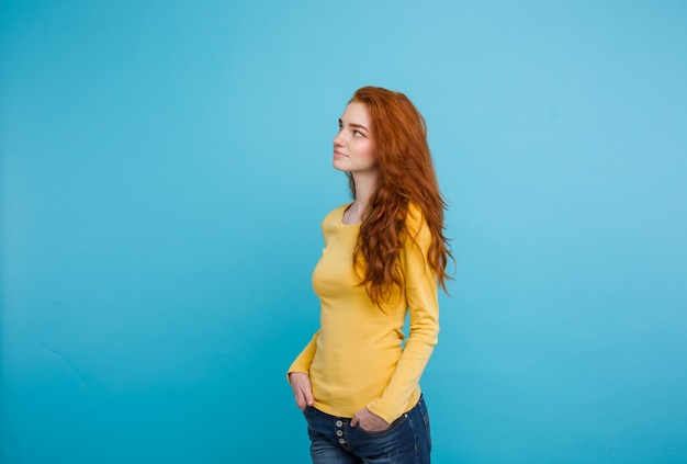 ライフスタイルの概念 - クローズアップ肖像画若い美しい魅力的なジンジャー赤毛の女の子は、shynessと彼女の髪を再生する。青いパステルの背景。スペースをコピーします。