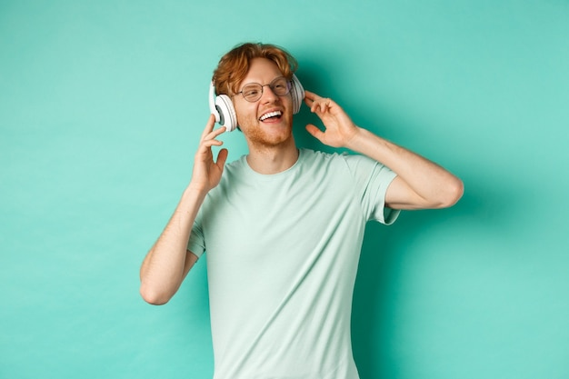 Lifestyle concept. happy young man with ginger hair dancing and having fun, listening music on wireless headphones and smiling pleased, turquoise background.